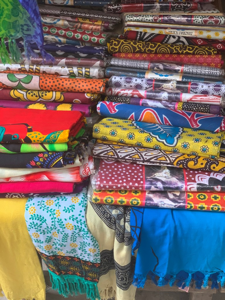 stack of fabrics in the market in stone town by sarah ambitious