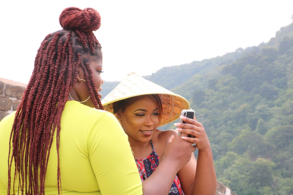 a picture of Sarah and Jemimah looking at a picture of themselves on the Great Wall of China.